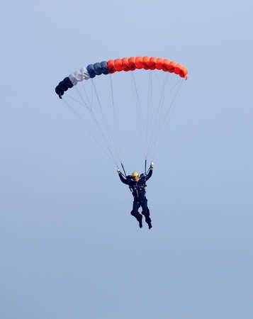 RUSTENBURG, SOUTH AFRICA - April 28, 2017: National Skydiving Championships. Male sky diver with brightly coloured open parachute gliding in air