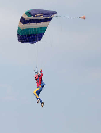 float cloud: RUSTENBURG, SOUTH AFRICA - April 28, 2017: National Skydiving Championships. Male sky diver with brightly coloured open parachute gliding in air