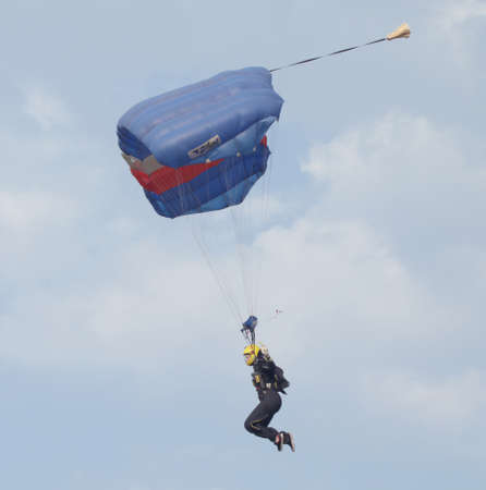 RUSTENBURG, SOUTH AFRICA - April 28, 2017: National Skydiving Championships. Female sky diver with brightly coloured open parachute landing at speed