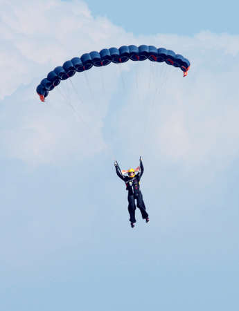 RUSTENBURG, SOUTH AFRICA - April 28, 2017: National Skydiving Championships. Female sky diver with bright blue open parachute.