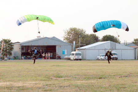 float cloud: RUSTENBURG, SOUTH AFRICA - April 28, 2017: National Skydiving Championships. Two skydivers landing simultaneously next to each other with open parachutes. Editorial