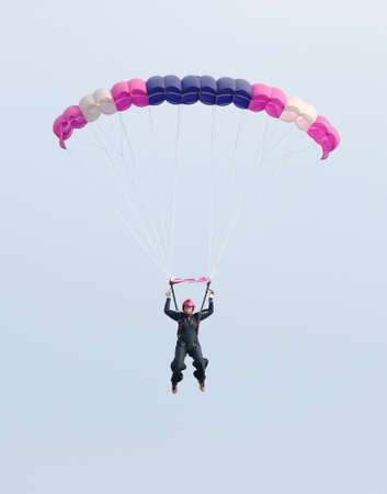 RUSTENBURG, SOUTH AFRICA - April 28, 2017: National Skydiving Championships. Female sky diver with brightly coloured open parachute gliding in air