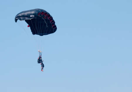 RUSTENBURG, SOUTH AFRICA - April 28, 2017: National Skydiving Championships. Jumper with black open parachute - text area available