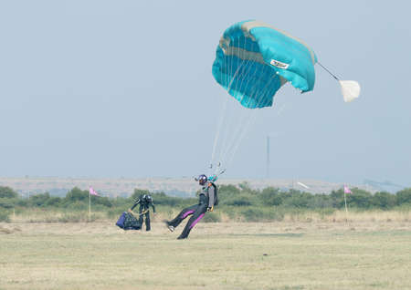 float cloud: RUSTENBURG, SOUTH AFRICA - April 28, 2017: National Skydiving Championships. Black African male skydiver making safe landing on grass with open brightly colourful parachute.
