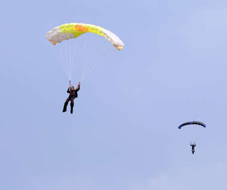 RUSTENBURG, SOUTH AFRICA - April 28, 2017: National Skydiving Championships. Two skydivers with colourful chutes approaching landing area in queue.