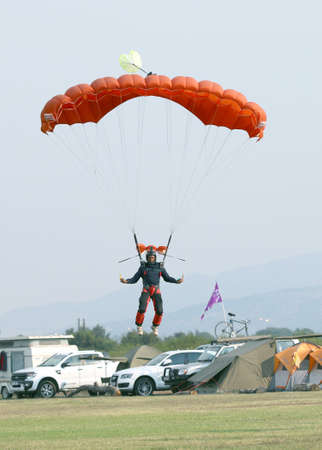 RUSTENBURG, SOUTH AFRICA - April 28, 2017: National Skydiving Championships. Black African male skydiver coming in for landing on grass with open bright colourful parachute.