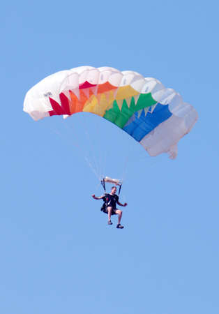 RUSTENBURG, SOUTH AFRICA - April 28, 2017: National Skydiving Championships. Male sky diver with brightly coloured open parachute preparing for landing