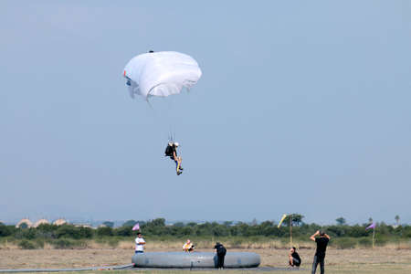 float cloud: RUSTENBURG, SOUTH AFRICA - April 28, 2017: National Skydiving Championships. Jumper with white open parachute performing Classic Accuracy landing. Editorial