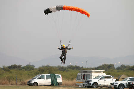 RUSTENBURG, SOUTH AFRICA - April 28, 2017: National Skydiving Championships. Male skydiver coming in for landing on grass with open brightly coloured parachute.