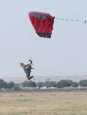 RUSTENBURG, SOUTH AFRICA - April 28, 2017: National Skydiving Championships. Male skydiver coming in for extra fast landing on grass with open brightly coloured parachute.