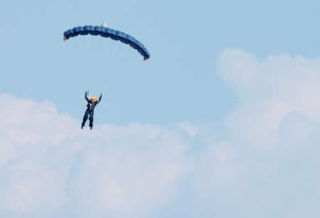 RUSTENBURG, SOUTH AFRICA - April 28, 2017: National Skydiving Championships. Sky diver against clouds with bright blue open parachute - text area available