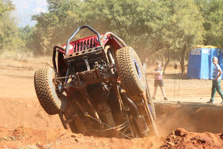 Rustenburg, South Africa – JUNE 17, 2017: National Extreme Modified 4x4 Vehicle Championship. Spectacular shot of undercarriage of red car ramping out of steep dugout with front wheels suspended in air.