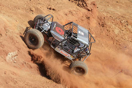 Rustenburg, South Africa – JUNE 17, 2017: National Extreme Modified 4x4 Vehicle Championship. Black Car powering up steep hill, kicking up sand and dust.