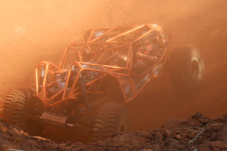 Rustenburg, South Africa – JUNE 17, 2017: National Extreme Modified 4x4 Vehicle Championship. Orange roll caged car in dugout with red dust suspended in air.