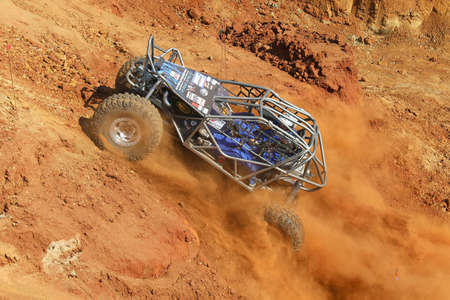 Rustenburg, South Africa – JUNE 17, 2017: National Extreme Modified 4x4 Vehicle Championship. Blue Car powering up steep hill, kicking up sand and dust. Editorial