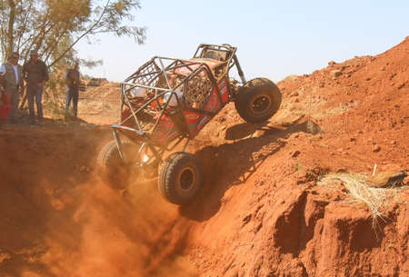 Rustenburg, South Africa – JUNE 17, 2017: National Extreme Modified 4x4 Vehicle Championship. Red car ramping out of steep dugout, three wheels suspended, kicking up sand and dust.