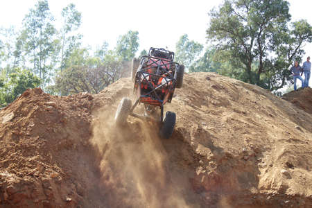 Rustenburg, South Africa – JUNE 17, 2017: National Extreme Modified 4x4 Vehicle Championship. Red Car ramping up against very steep hill, front wheels suspended, kicking up sand and dust. Editorial