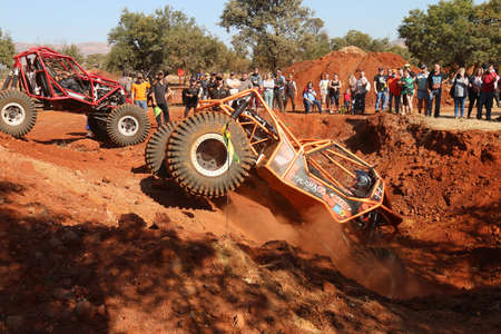 Rustenburg, South Africa – JUNE 17, 2017: National Extreme Modified 4x4 Vehicle Championship. Car ramping out steep dugout, front wheels suspended, kicking up sand and dust. Editorial