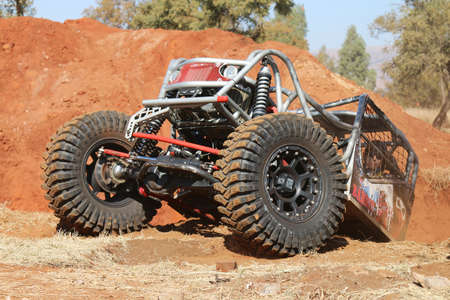Rustenburg, South Africa – JUNE 17, 2017: National Extreme Modified 4x4 Vehicle Championship. Red Car climbing out steep dugout, front tires gripping on flat surface.