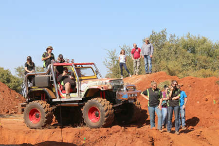 Rustenburg, South Africa – JUNE 17, 2017: National Extreme Modified 4x4 Vehicle Championship. Event commentator on big foot large 4x4 with spectators looking at event.