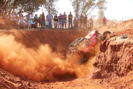 modified: Rustenburg, South Africa – JUNE 17, 2017: National Extreme Modified 4x4 Vehicle Championship. Red Car climbing out steep dugout, kicking up sand and dust with spectators looking on.