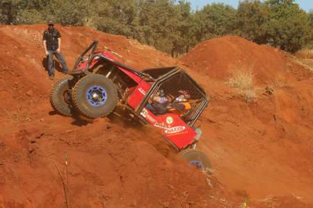 Rustenburg, South Africa - JUNE 17, 2017: National Extreme Modified 4x4 Vehicle Championship. Red car powering up steep hill, kicking up sand and dust, marshal watching. Editorial