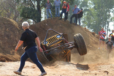 Rustenburg, South Africa - JUNE 17, 2017: National Extreme Modified 4x4 Vehicle Championship. Spectators watching yellow car shooting with suspended front wheels out of dugout. Editorial