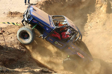 Rustenburg, South Africa - JUNE 17, 2017: National Extreme Modified 4x4 Vehicle Championship. Blue Car powering up steep hill, kicking up sand and dust.