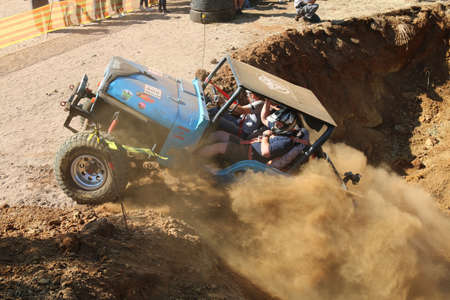 Rustenburg, South Africa - JUNE 17, 2017: National Extreme Modified 4x4 Vehicle Championship. Spectators watching blue car powering out of dugout, kicking up sand and dust. Editorial