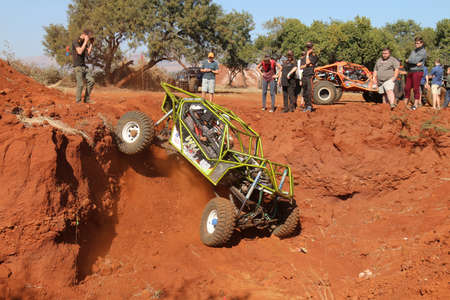 Rustenburg, South Africa - JUNE 17, 2017: National Extreme Modified 4x4 Vehicle Championship. Metallic Green rol cage car descending very steep drop into dugout.