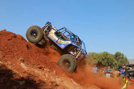 Rustenburg, South Africa - JUNE 17, 2017: National Extreme Modified 4x4 Vehicle Championship. Blue car powering up steep sand mountain, front wheels suspended, kicking up sand and dust.