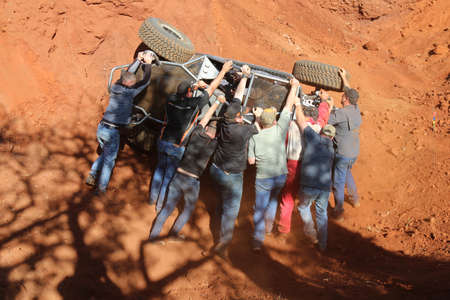 Rustenburg, South Africa - JUNE 17, 2017: National Extreme Modified 4x4 Vehicle Championship. Black car rolling in dugout sequence of photos. Car turned upright by marshals. 6 of 6