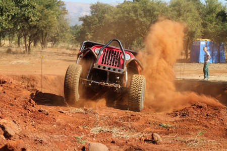 Rustenburg, South Africa - JUNE 17, 2017: National Extreme Modified 4x4 Vehicle Championship. Red Car climbing out steep dugout, front wheels suspended, kicking up sand and dust. Editorial