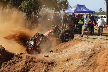 Rustenburg, South Africa - JUNE 17, 2017: National Extreme Modified 4x4 Vehicle Championship. Spectators watching orange car powering out of dugout, kicking up sand and dust.