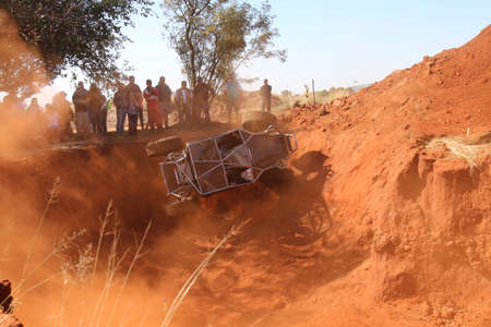 Rustenburg, South Africa - JUNE 17, 2017: National Extreme Modified 4x4 Vehicle Championship. Black car rolling in dugout sequence of photos. Car starting to topple. 1 of 6