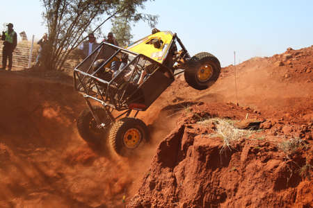 Rustenburg, South Africa - JUNE 17, 2017: National Extreme Modified 4x4 Vehicle Championship. Yellow car ramping out of steep dugout, front wheels suspended, kicking up sand and dust.
