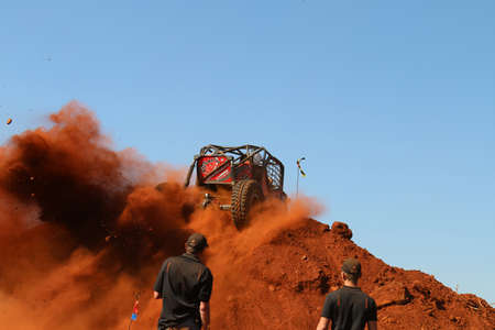 Rustenburg, South Africa - JUNE 17, 2017: National Extreme Modified 4x4 Vehicle Championship. Blue sky with red car spinning over steep sand mountain, kicking up sand and dust.