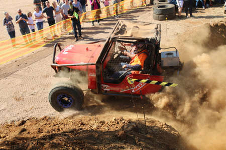 Rustenburg, South Africa - JUNE 17, 2017: National Extreme Modified 4x4 Vehicle Championship. Spectators watching red car powering out of dugout, kicking up sand and dust.