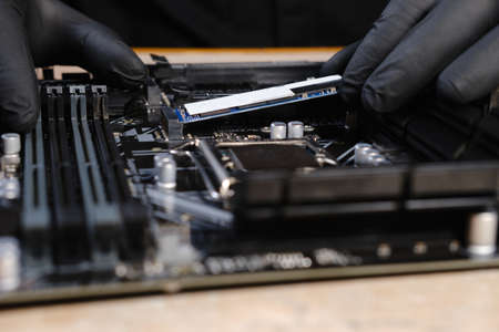 Engineer repairman holding hands in black gloves hard drive SSD to insert into the computer or laptop
