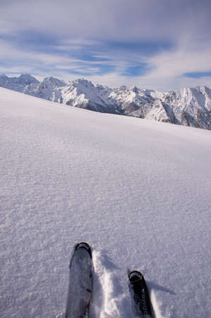 deep powder snow: A pair of skis in deep, fresh snow with mountains in the background. Stock Photo