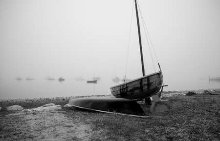 ocea: Black and white of a small boat on a beach on a misty morning. Stock Photo