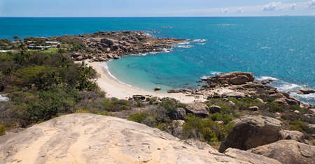 whitsundays: Looking down on horseshoe bay in Bowen, the water is bright blue and the beach is empty. Stock Photo