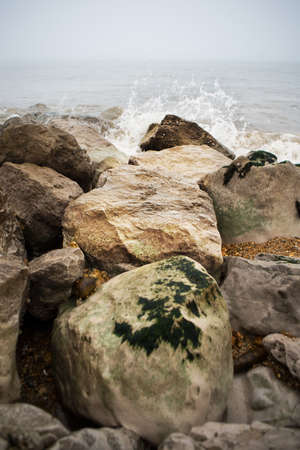 atmospheric: Waves crash against a cluster of rocks on the Dorset coast, the weather is misty and atmospheric. Stock Photo