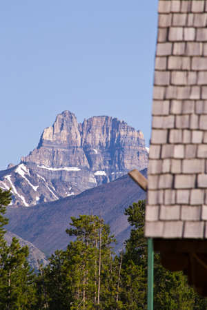 lingering: The face of a mountain with some snow lingering in the shade behind a tiled roof in sunlight.