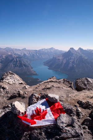 north cascade national park: The Canadian flag at the top of a mountain, looking down on a turquoise glacial lake and other mountains in the summer.