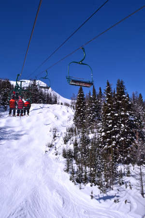ski run: A chairlift going over a ski run with blue skies above. Stock Photo