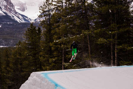 black ski pants: A skier doing a jump next to trees, the skier is spinning in the air