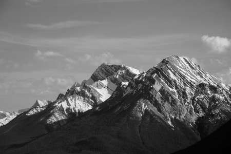 jagged: A black and white picture of a jagged mountain with pockets of snow in the shaded spots.