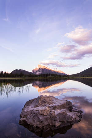 protruding: A large rock protruding from a flat, clear lake with a mountain in the background. Stock Photo
