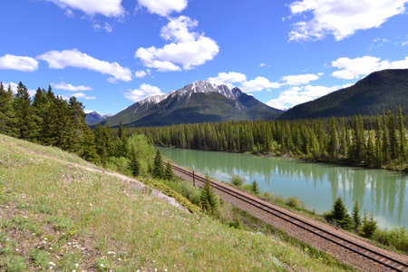 canadian rockies: Railway tracks next to a turquoise river in the Canadian rockies